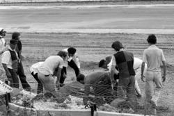 Del personale della St John Ambulance e altri aiutanti portano via il corpo di Tom Pryce, Shadow