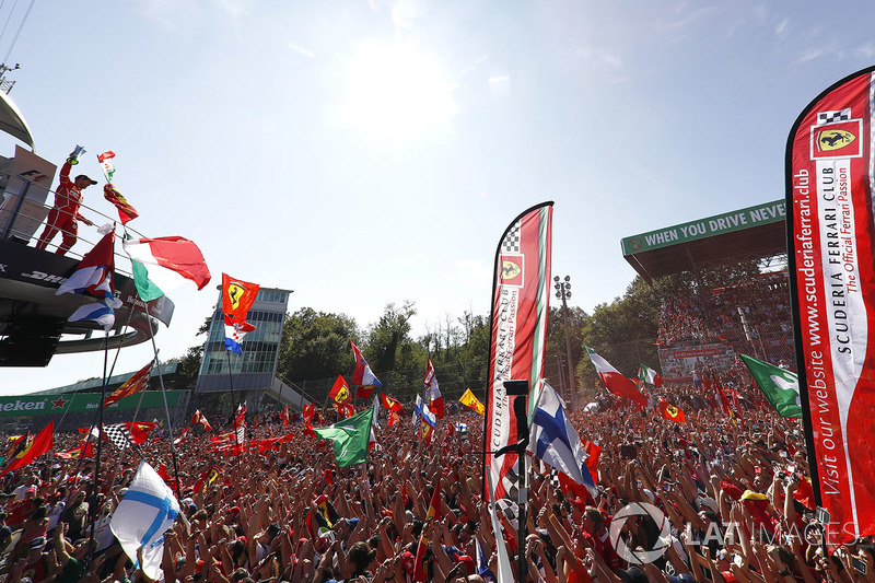 A sea of red clothes and red smoke gathers around the podium to cheer for Third place Sebastian Vettel, Ferrari