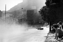 Cars pass through the smoke from Lorenzo Bandini, Ferrari 312 accident