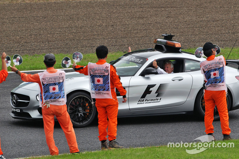 Marhals wave at Charlie Whiting, FIA Delegate in the FIA Safety Car