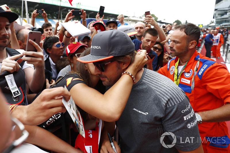 Fernando Alonso, McLaren, is greeted by a friendly fan