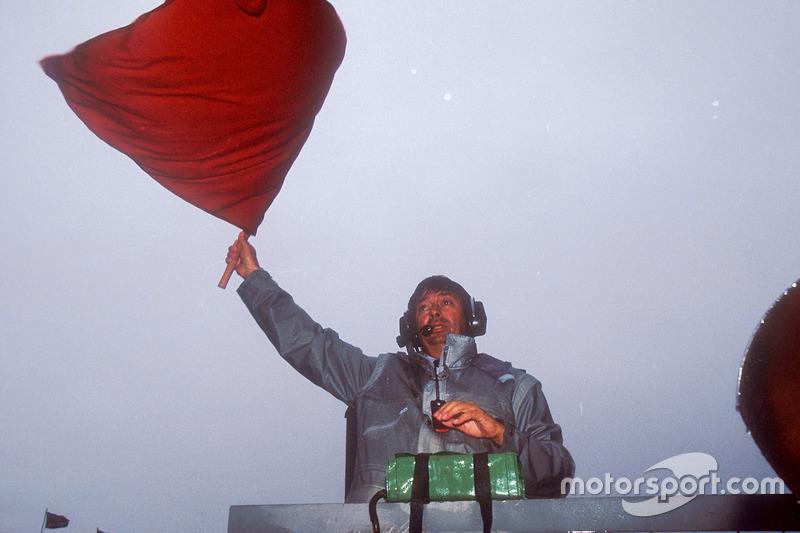 Arracada: Roland Bruynseraede agita la bandera roja para detener la carrera tras 15 vueltas, debido a las lluvias torrenciales que hicieron atroces condiciones de conducción