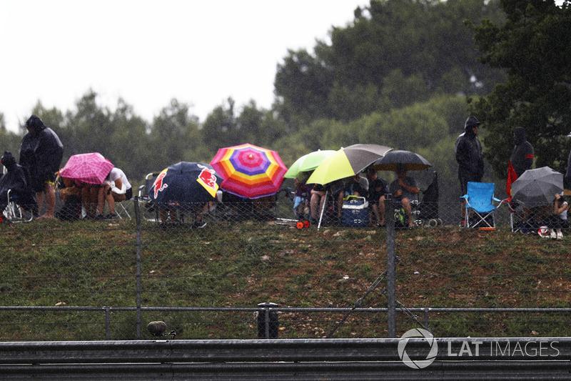 Penonton membuka payung mereka