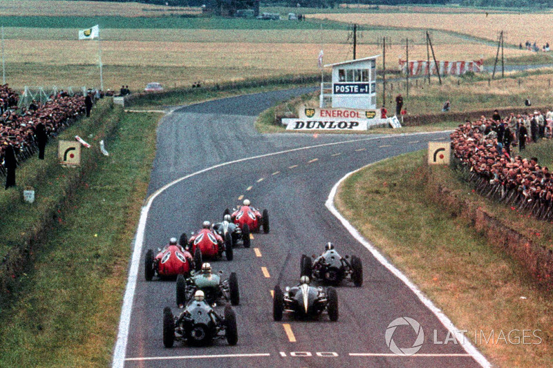 The Ferrari D246 of Phil Hill, leads Jack Brabham, Cooper Climax T53, and the two Ferrari D246 of Wolfgang von Trips, and Willy Mairesse, into the first corner after the start