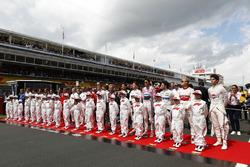 Los pilotos se paran con los niños de la cuadrícula para el himno nacional