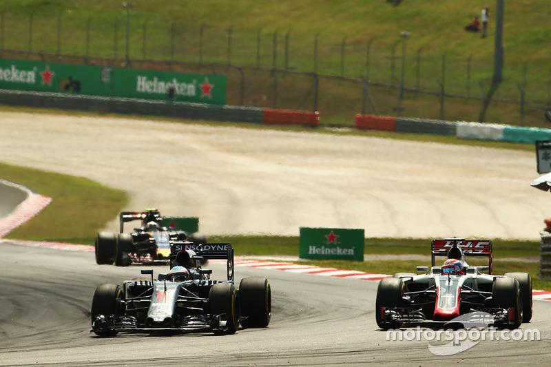 (L to R): Fernando Alonso, McLaren MP4-31 and Romain Grosjean, Haas F1 Team VF-16 battle for positio