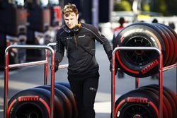 Un meccanico McLaren trascina due carrelli di pneumatici Pirelli
