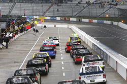 Trucks follow the pace car down pit road after the race is stopped on lap 23 of 250