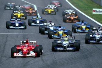The start of the race and Michael Schumacher, Ferrari, leads Ralf Schumacher, Williams BMW FW24, Juan Pablo Montoya, Williams BMW FW24