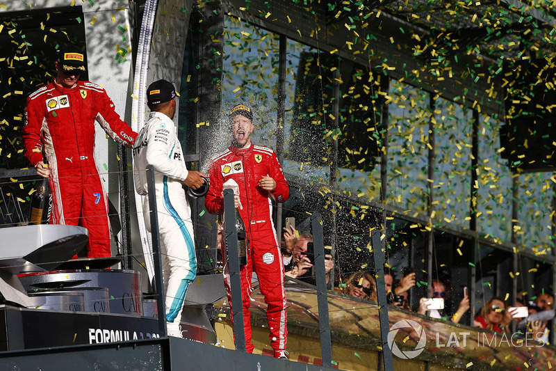 Kimi Raikkonen, Ferrari, 3rd position, Lewis Hamilton, Mercedes AMG F1, 2nd position, and Sebastian Vettel, Ferrari, 1st position, celebrate with Champagne on the podium