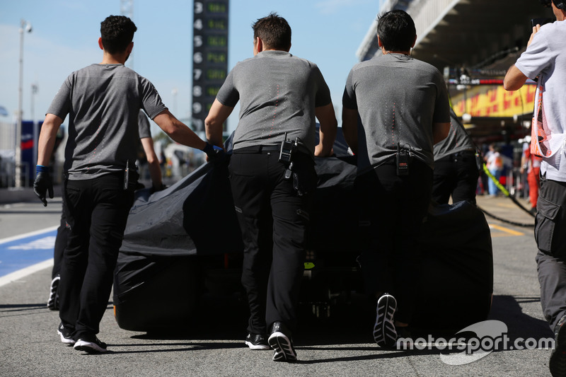 Инженеры McLaren катят накрытый покрывалом McLaren MCL32 Фернандо Алонсо по пит-лейну