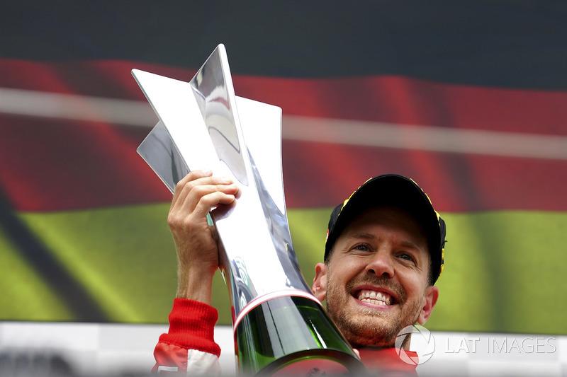 Sebastian Vettel, Ferrari, 1st position, celebrates on the podium with his trophy