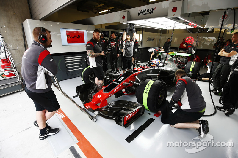 The Haas F1 Team team make adjustments to the car of Romain Grosjean, Haas F1 Team VF-17, in the garage
