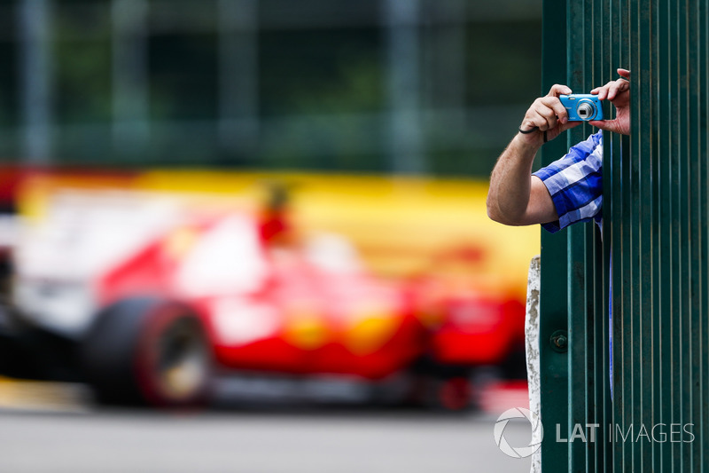 A fan leans through some bars to take a photo as Sebastian Vettel, Ferrari SF70H, passes by in the background