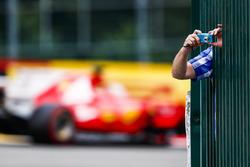 Un fan si sporge dalla barriera per scattare una foto mentre Sebastian Vettel, Ferrari SF70H, passa