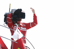 Third place Sebastian Vettel, Ferrari, borrows a TV camera to film the crowd from the podium