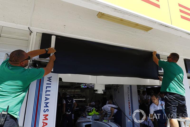 Los trabajadores cambian las placas de nombre de Felipe Massa, Williams, a Paul di Resta
