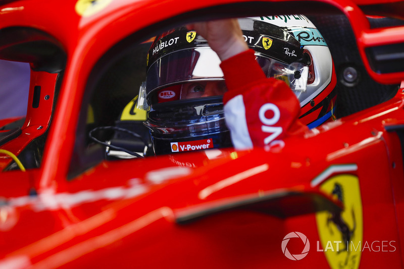 Kimi Raikkonen, Ferrari, in cockpit, reaches towards his halo