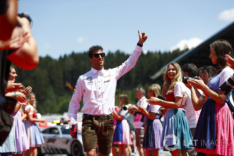 Daniel Ricciardo, Red Bull Racing, gives a thumbs up as he walks down a corridor of dirndl wearing grid girls