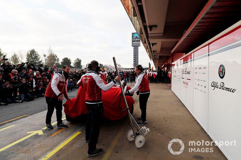 Les mécaniciens Alfa Romeo Racing avec l'Alfa Romeo Racing C38 sous un drap
