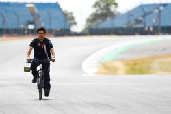 A Force India team member cycles the track