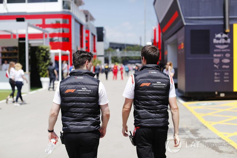 Dos hombres vestidos con ropa de marca TATA caminan por el paddock