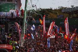 Confetti and streamers fall around the huge crowd of Ferrari fans gathered for the podium ceremony