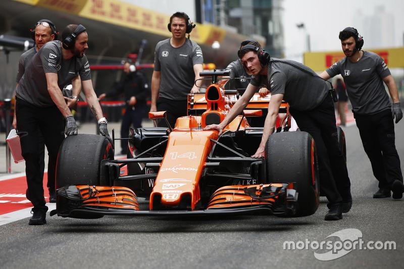 McLaren team members move the car of Fernando Alonso, McLaren MCL32