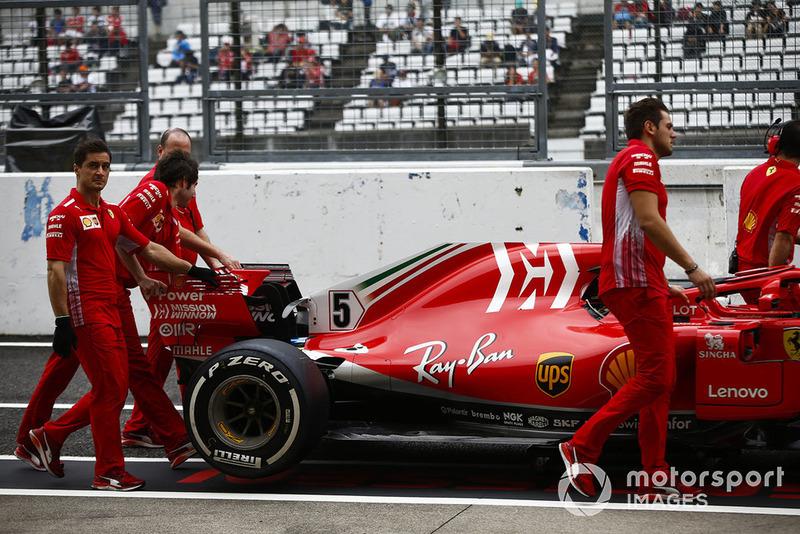 Mekanik Ferrari mendorong mobil Sebastian Vettel, Ferrari SF71H, di pit lane