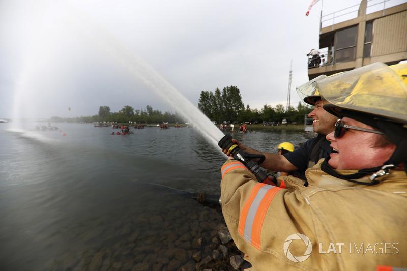 Пожарные поливают водой участников гонки на плотах