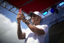 Lewis Hamilton, Mercedes AMG F1, takes a photo of the crowd