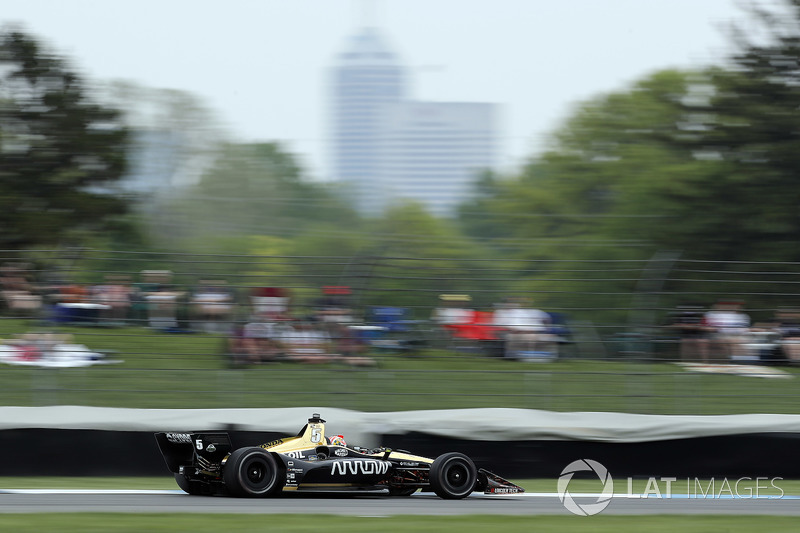 Hinchcliffe hurtles down the IMS road course back straight, with downtown Indianapolis looming through the gloom in the background.