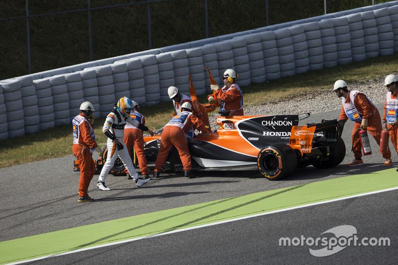 Oficiales de pista asisten a Fernando Alonso, McLaren MCL32 al tener con problemas de motor