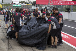 The crashed car of Romain Grosjean, Haas F1 Team VF-17 is returned to the pits