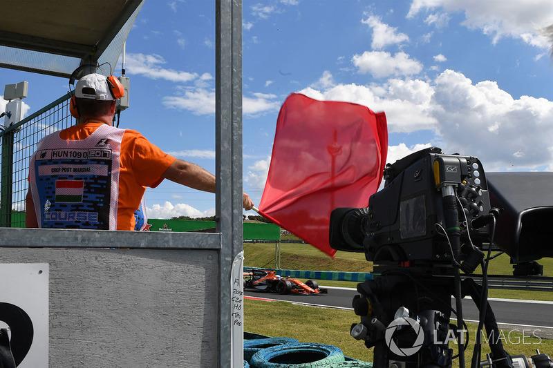 Oficiales de pista ondean la bandera roja