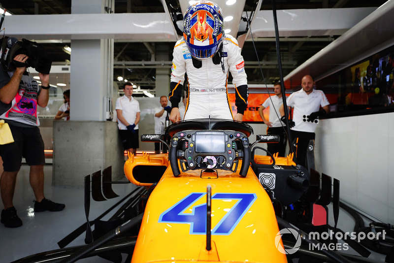 Lando Norris, McLaren MCL33, climbs into the car in the garage