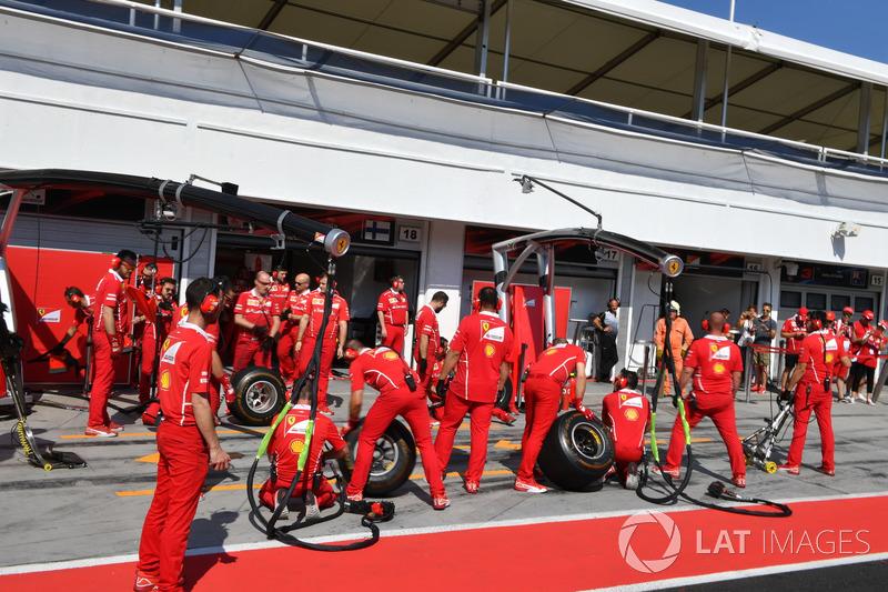 Mecánicos de Ferrari esperan una parada en boxes