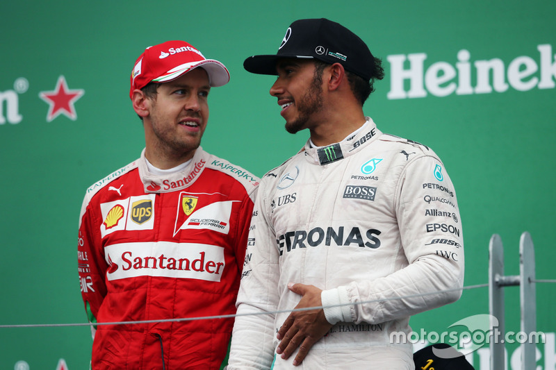 (Зліва направо): Себастьян Феттель, Ferrari з переможецем гонки Льюїс Хемілтон, Mercedes AMG F1, на подіумі