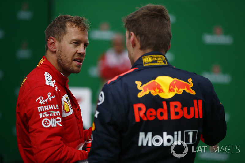 Sebastian Vettel, Ferrari, talks to Max Verstappen, Red Bull Racing