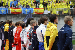 The drivers stand for the national anthem prior to the race start