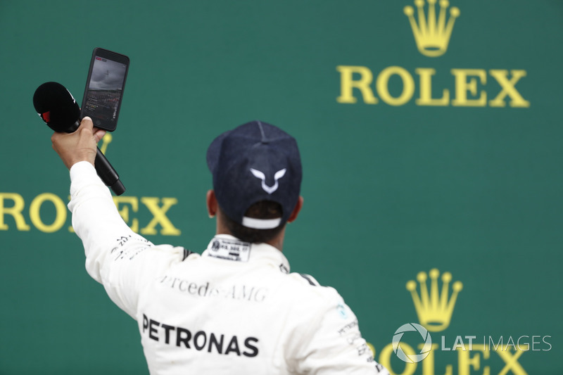 Podium:  Race winner Lewis Hamilton, Mercedes AMG F1, takes a photo, the crowd in the background