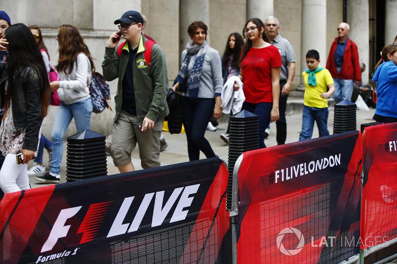 Los miembros del público a pie pasando barandas cubiertas de F1 Londres