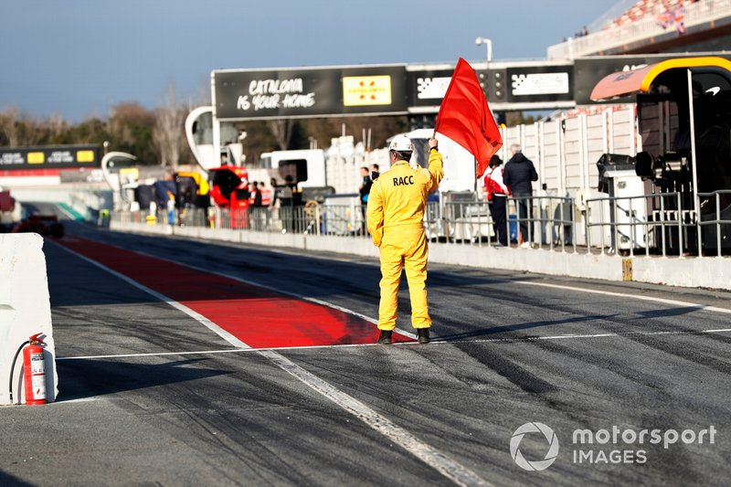 Marshal waves the red flag in pit lane