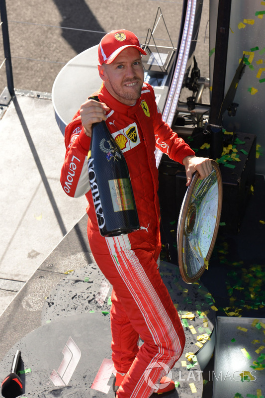 Race winner Sebastian Vettel, Ferrari celebrates on the podium with the trophy and the champagne