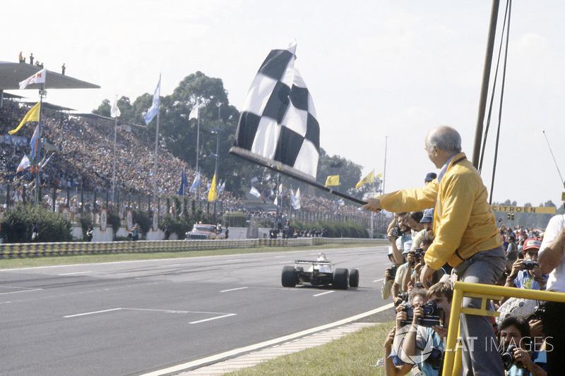Juan Manuel Fangio brandit le drapeau à damier pour Carlos Reutemann, Williams FW07C-Ford Cosworth