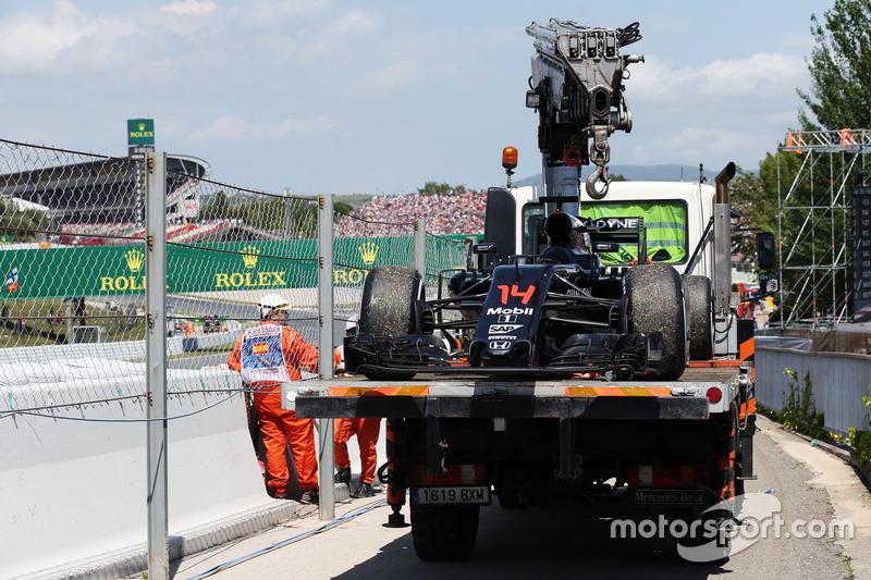 El McLaren MP4-31 de Fernando Alonso, es recuperado de la pista