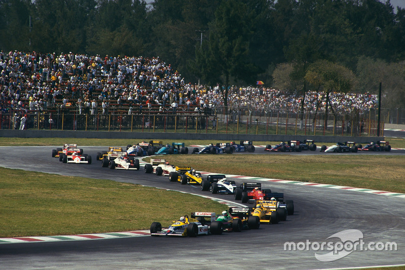 Nigel Mansell, Williams FW11B Honda, leads Teo Fabi, Benetton B187 Ford, Ayrton Senna, Lotus 99T Honda, and the rest of the field on the first lap