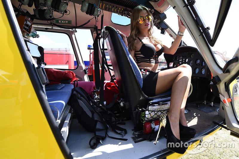 Grid girl in posa con un elicottero