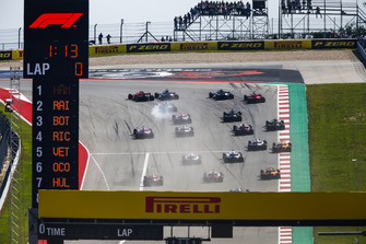 Kimi Raikkonen, Ferrari SF71H, passes Lewis Hamilton, Mercedes AMG F1 W09 EQ Power+, in the first turn as they lead the field at the start of the race