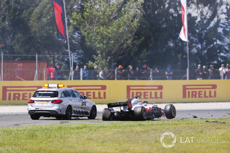 An official car stops next to the damaged Romain Grosjean Haas F1 Team VF-18